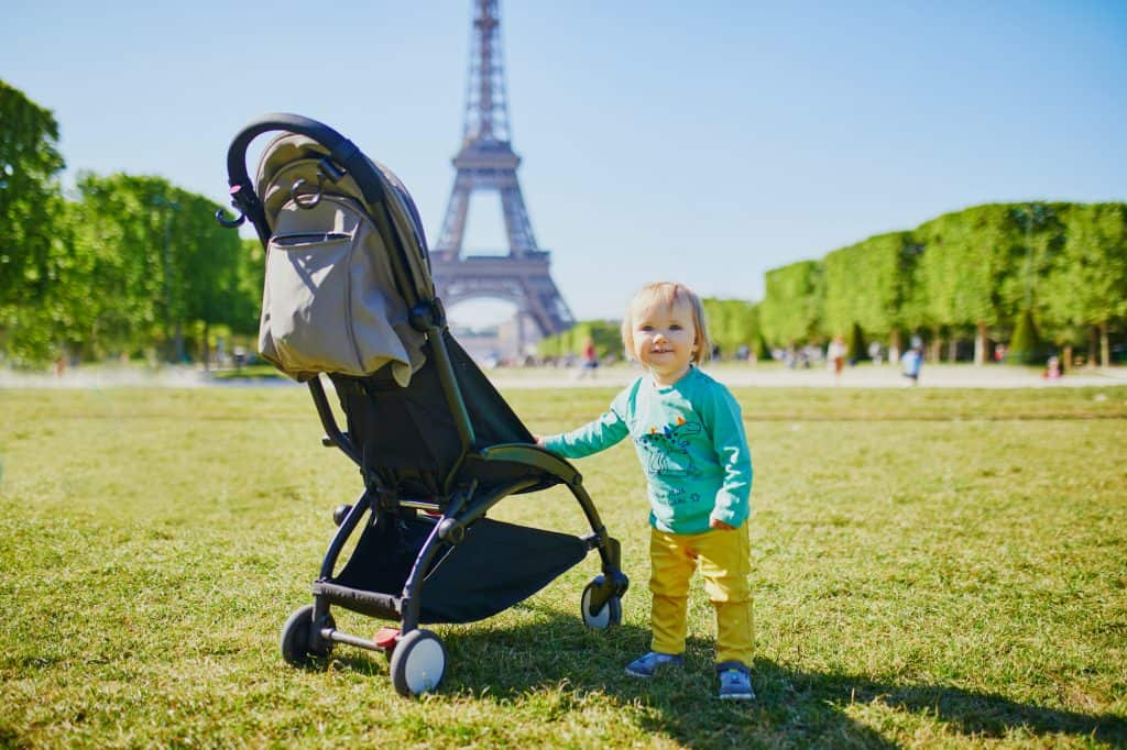 Child with stroller standing near the Eiffel Tower